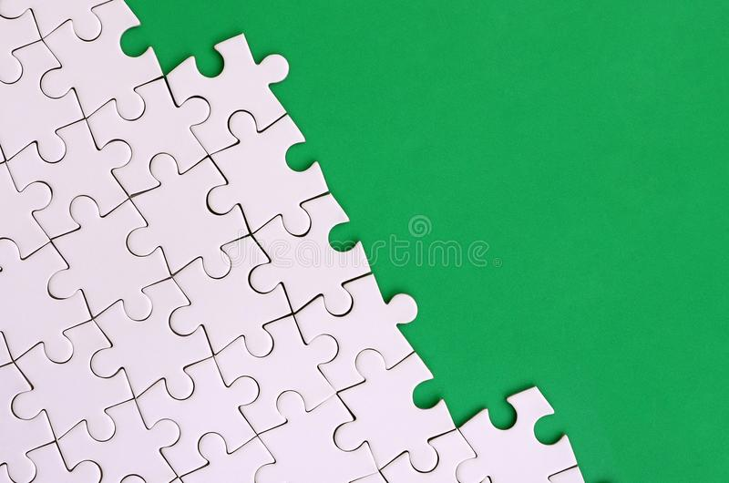 Fragment of a folded white jigsaw puzzle on the background of a green plastic surface. Texture photo with copy space for text.  royalty free stock photo