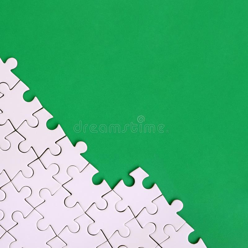 Fragment of a folded white jigsaw puzzle on the background of a green plastic surface. Texture photo with copy space for text.  stock image