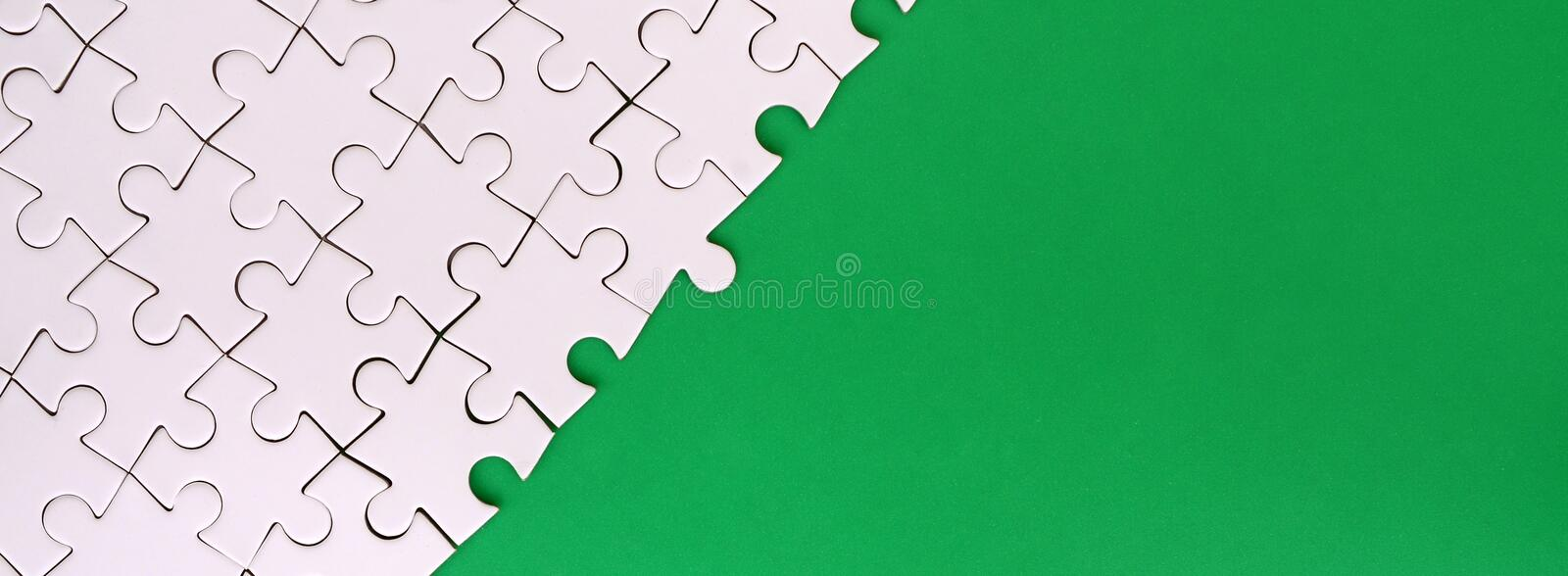 Fragment of a folded white jigsaw puzzle on the background of a green plastic surface. Texture photo with copy space for text.  royalty free stock image