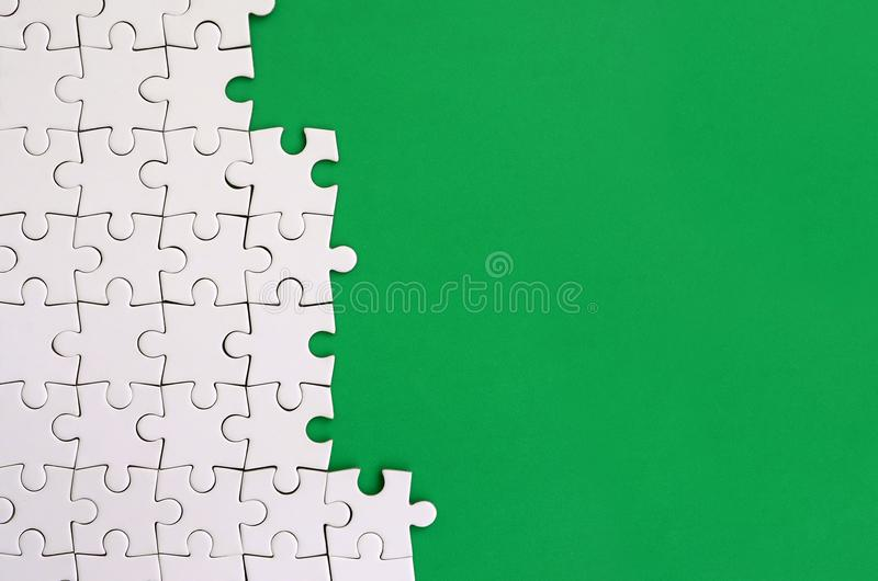 Fragment of a folded white jigsaw puzzle on the background of a green plastic surface. Texture photo with copy space for text.  royalty free stock images