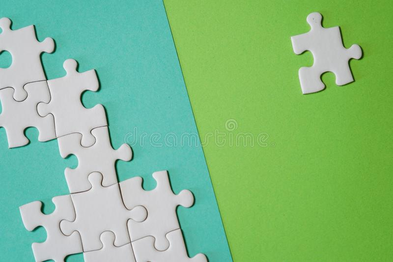 Fragment of a folded white jigsaw puzzle and a pile of uncombed puzzle elements against the background of a colored surface vector illustration