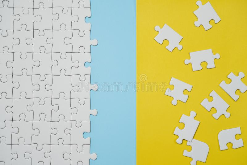 Fragment of a folded white jigsaw puzzle and a pile of uncombed puzzle elements against the background of a yellow surface stock image
