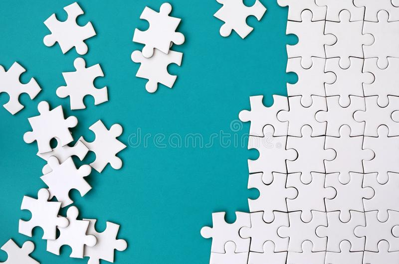 Fragment of a folded white jigsaw puzzle and a pile of uncombed puzzle elements against the background of a blue surface. Texture royalty free stock photography