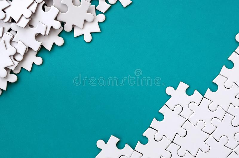 Fragment of a folded white jigsaw puzzle and a pile of uncombed puzzle elements against the background of a blue surface. Texture stock images