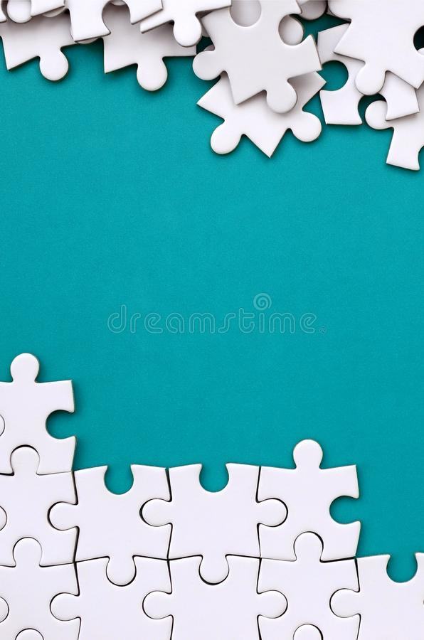 Fragment of a folded white jigsaw puzzle and a pile of uncombed puzzle elements against the background of a blue surface. Texture stock photography