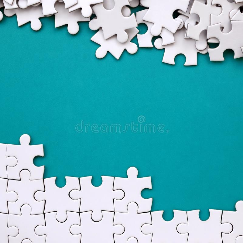 Fragment of a folded white jigsaw puzzle and a pile of uncombed puzzle elements against the background of a blue surface. Texture royalty free stock images