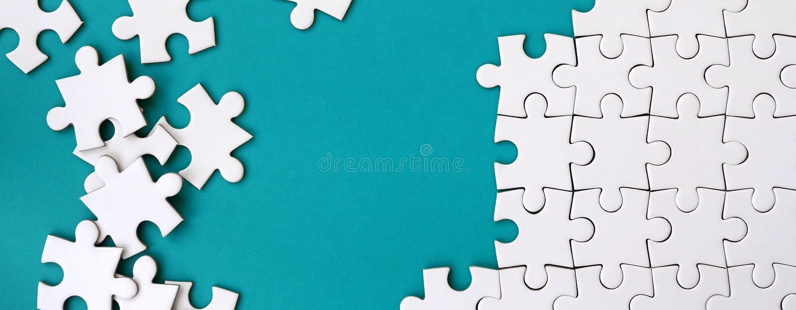 Fragment of a folded white jigsaw puzzle and a pile of uncombed puzzle elements against the background of a blue surface. Texture royalty free stock photo