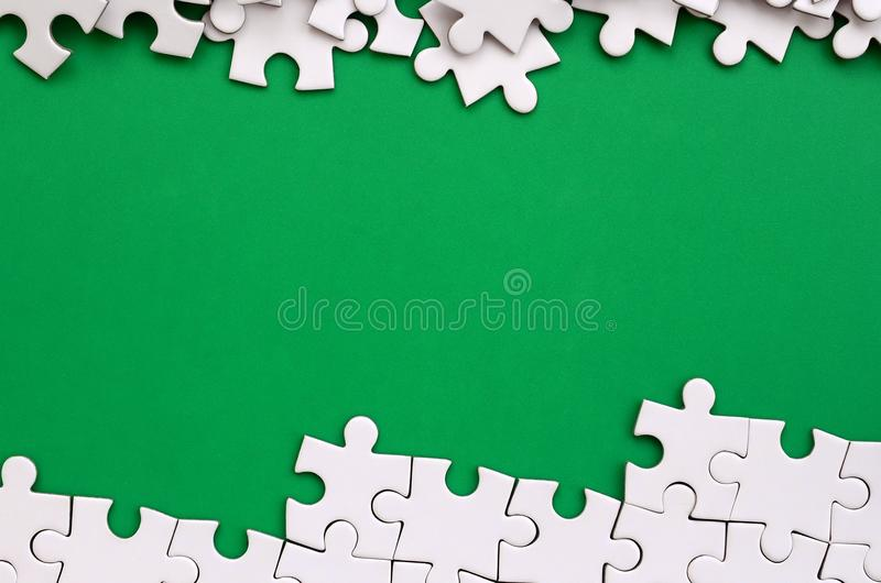 Fragment of a folded white jigsaw puzzle and a pile of uncombed puzzle elements against the background of a green surface. Texture. Photo with space for text stock photography