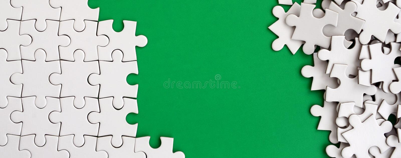 Fragment of a folded white jigsaw puzzle and a pile of uncombed puzzle elements against the background of a green surface. Texture. Photo with space for text royalty free stock image
