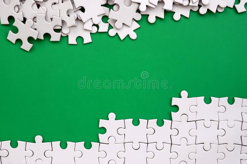 Fragment of a folded white jigsaw puzzle and a pile of uncombed puzzle elements against the background of a green surface. Texture stock image
