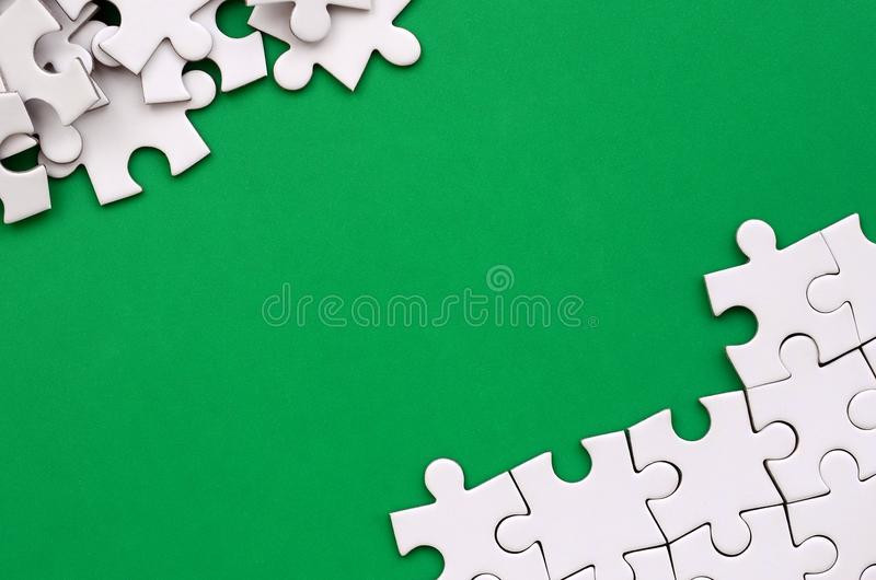 Fragment of a folded white jigsaw puzzle and a pile of uncombed puzzle elements against the background of a green surface. Texture. Photo with space for text royalty free stock photography