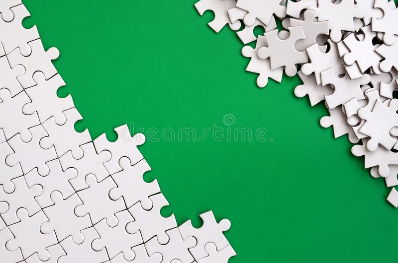 Fragment of a folded white jigsaw puzzle and a pile of uncombed puzzle elements against the background of a green surface. Texture. Photo with space for text royalty free stock photo