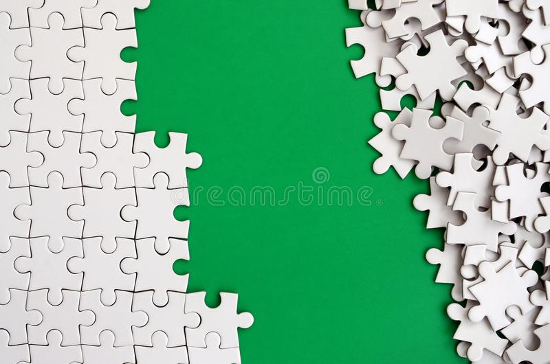 Fragment of a folded white jigsaw puzzle and a pile of uncombed puzzle elements against the background of a green surface. Texture. Photo with space for text stock image
