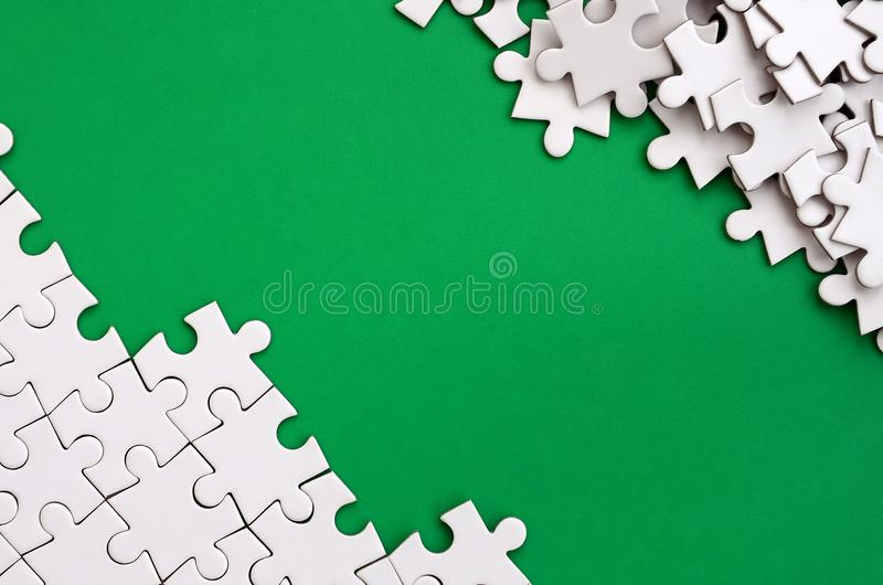 Fragment of a folded white jigsaw puzzle and a pile of uncombed puzzle elements against the background of a green surface. Texture. Photo with space for text royalty free stock images