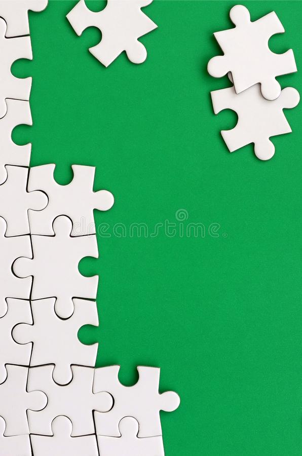 Fragment of a folded white jigsaw puzzle and a pile of uncombed puzzle elements against the background of a green surface. Texture. Photo with space for text royalty free stock photos