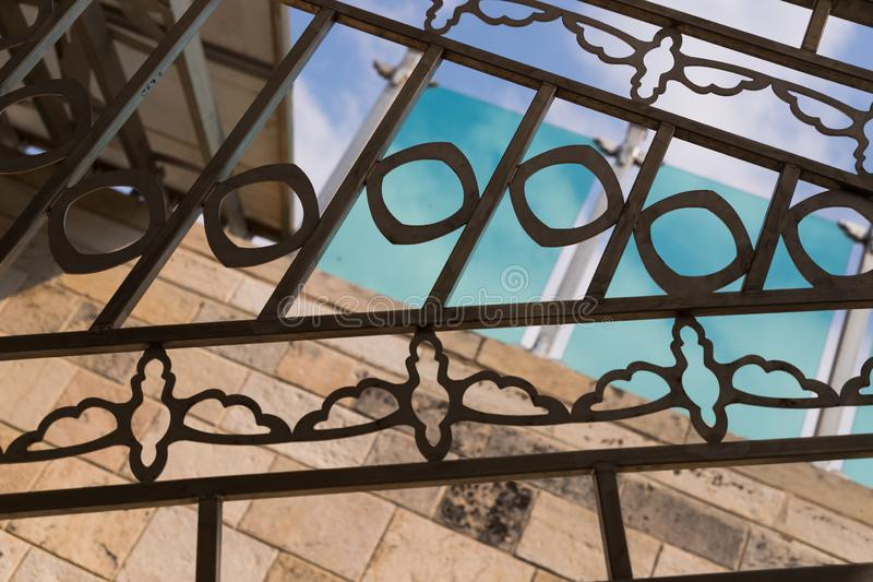 Fragment of forged decorative iron fence. Decorative forged steel grating. Vintage forging in the Austrian Hospice in stock photography