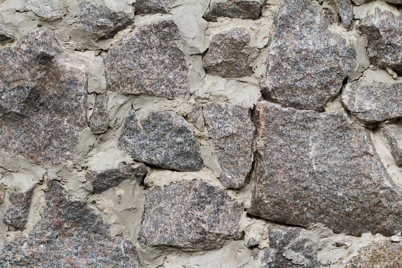 Fragment of gray stone wall with cement solution. Front view stock photo