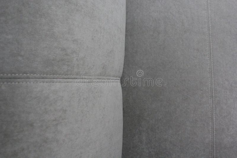Fragment of a gray velour sofa. Seams on the back and seat stock photo