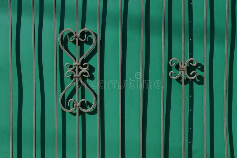 Fragment of a green fence with forged bars and a beautiful pattern. The texture of a green metal fence and steel bars with a pattern stock photography
