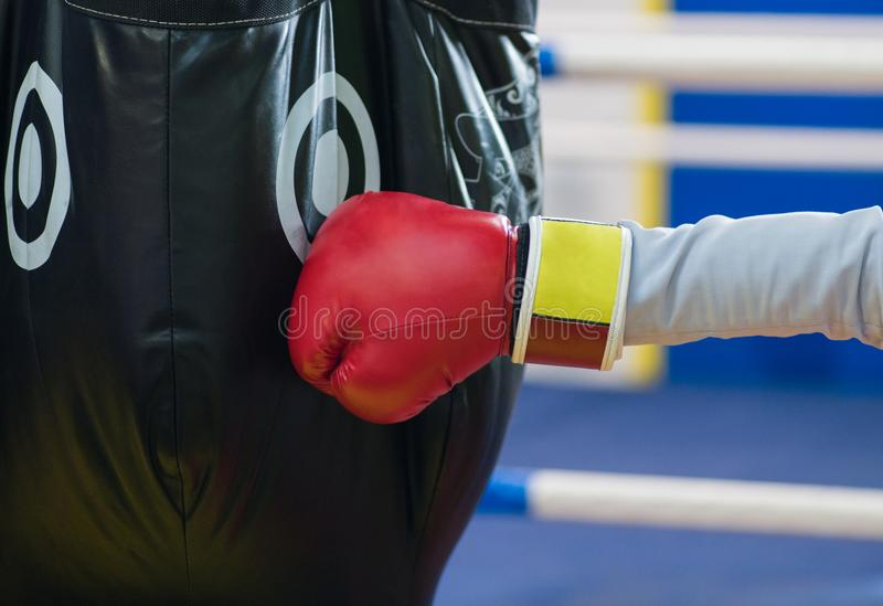 A fragment of a hand in a Boxing red glove hits a black pear. Th royalty free stock image