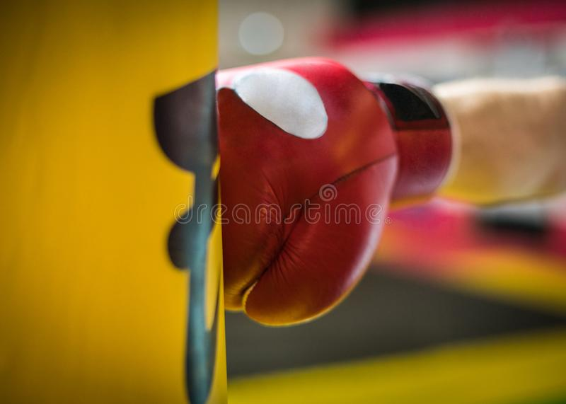 A fragment of the hand in the Boxing red glove hits the yellow p royalty free stock images