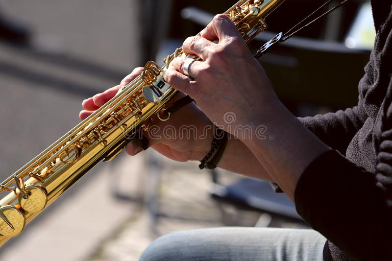Fragment of the hands of an old street musician. An image of the hands of a musician male pressing a saxophone button. stock image