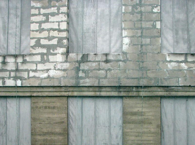 Fragment of industrial building loft wall with windows. Fragment of industrial building brick loft wall with big windows under reconstruction mesh stock photo