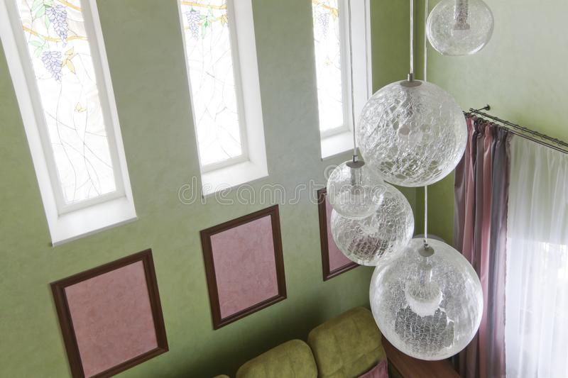 Fragment of the interior with a green sofa and picture cards. Interior in green colors and a glass chandelier. New renovation in the cottage stock photos