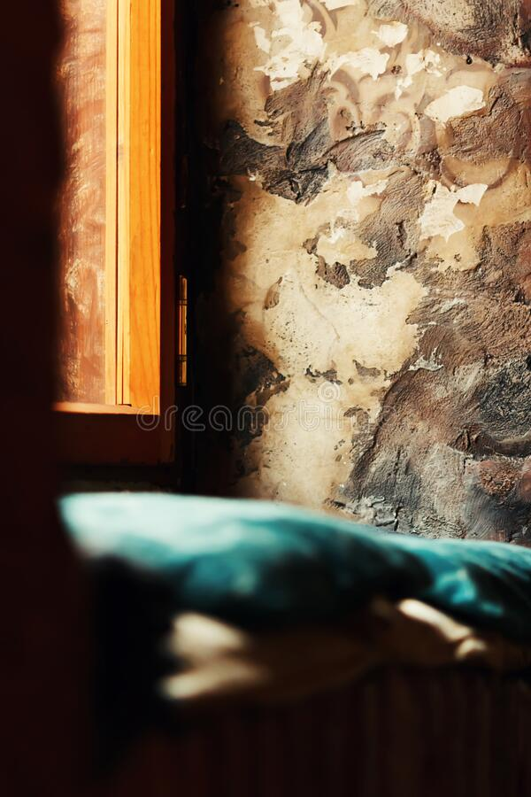 Fragment of interior space near the window with textured wall, torques pillows and window natural sunlight royalty free stock images