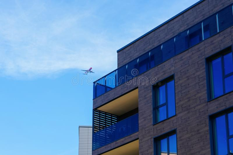 Fragment of Modern architecture of residential building and airplane royalty free stock photo