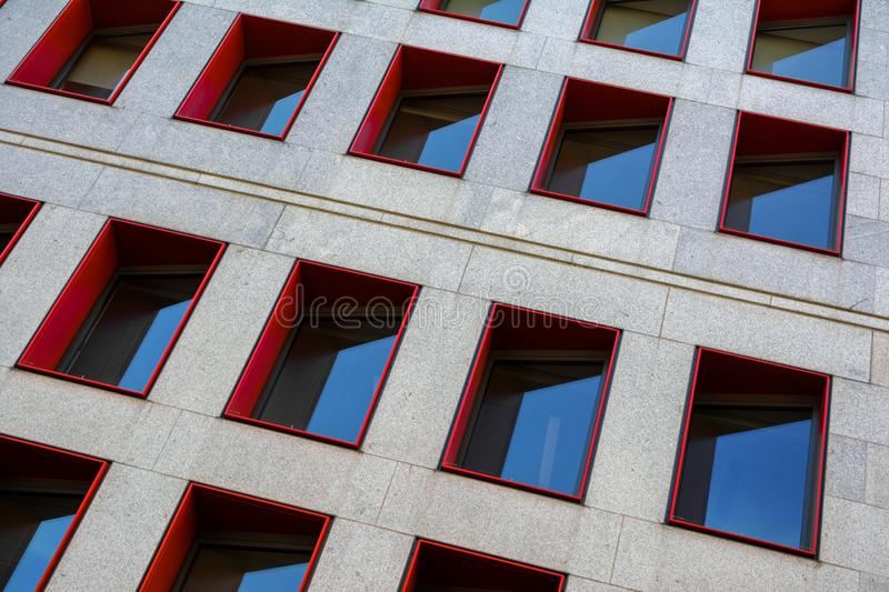 Fragment of modern building facade with red window frames stock image