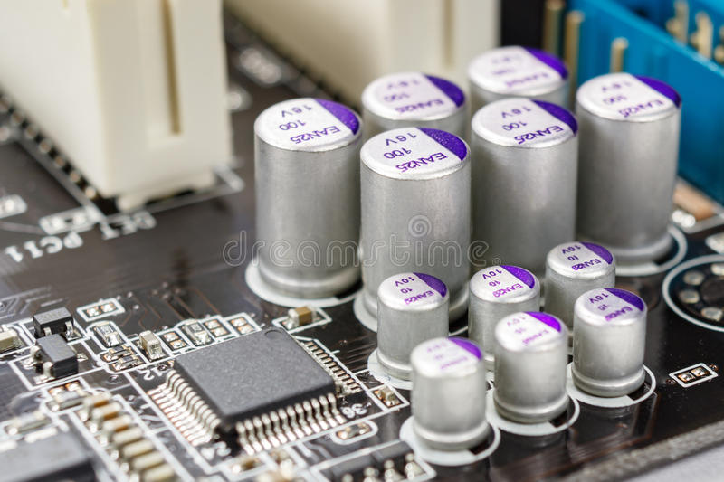 Fragment of the motherboard with the installed electrolytic capacitors closeup royalty free stock photos
