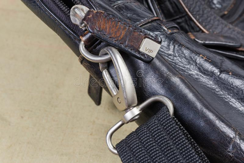 Fragment of old black handbag with some metal bag accessories. Fragment of the old shabby black men`s leather handbag with bag accessories - zipper with leather stock photo