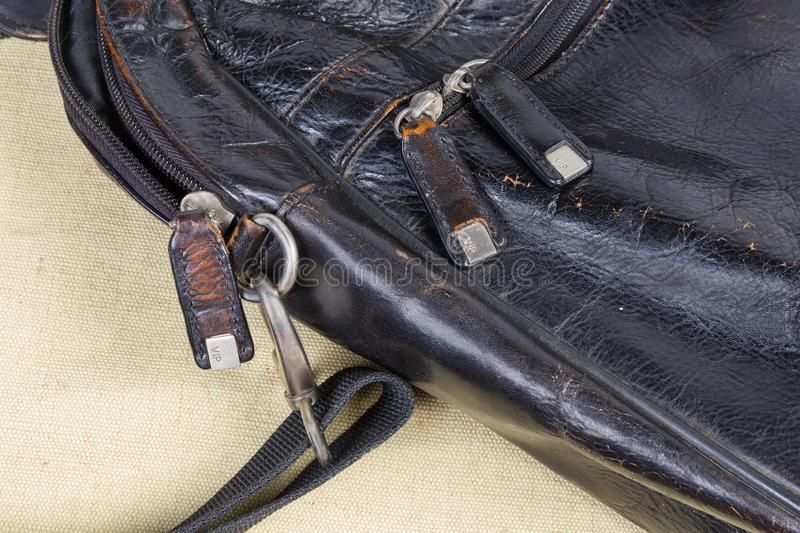 Fragment of old black leather handbag with some bag accessories. Fragment of the old shabby black men`s leather handbag with bag accessories - zippers with stock photography