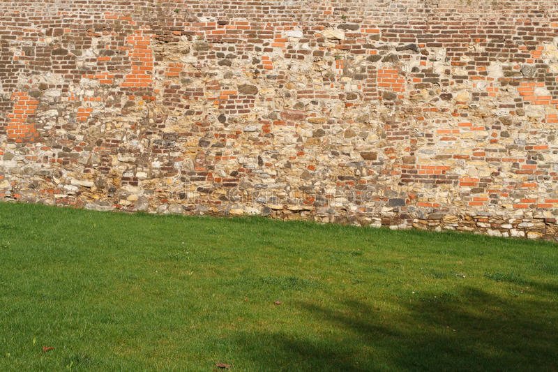 Fragment of old brick fortress wall. And green grass royalty free stock photo