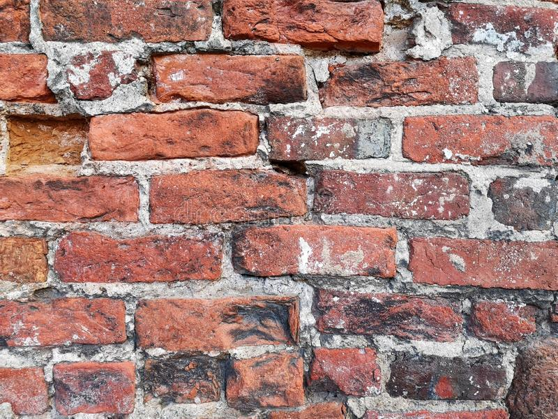 Fragment of an old bricked wall with cement joints. Background. Ancient, weathered, rough, uneven, medieval, chipped, retro, vintage, surface, nobody, outdoor royalty free stock photo