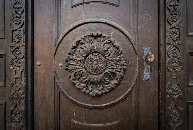 Fragment of an old door decorated with wood carvings stock photos