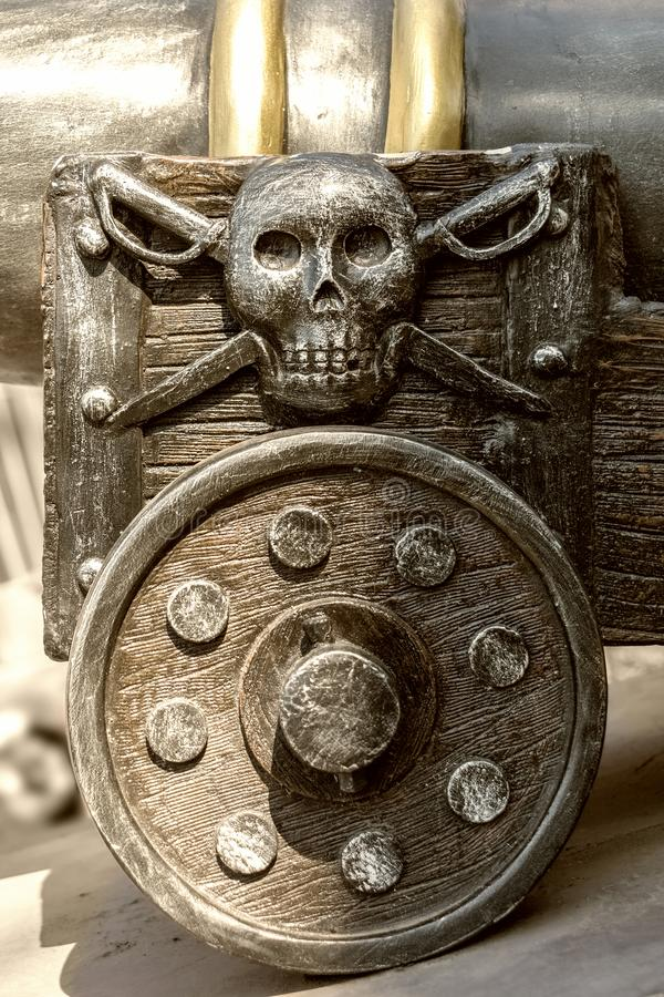 Fragment of an old gun carriage with a pirate emblem. royalty free stock photo