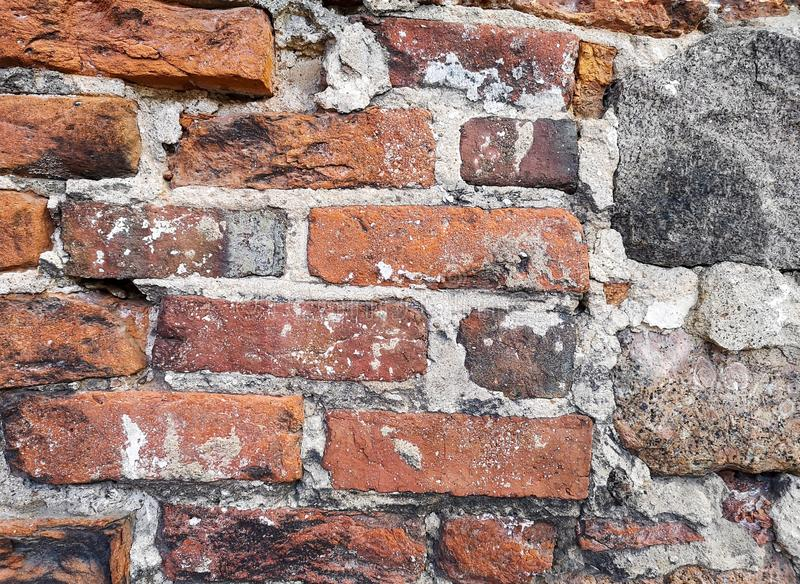 Fragment of an old historical wall made of brick and natural stone. Background royalty free stock images
