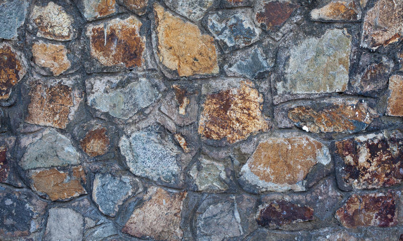 Fragment of old stone wall close-up. Textural background stock photography
