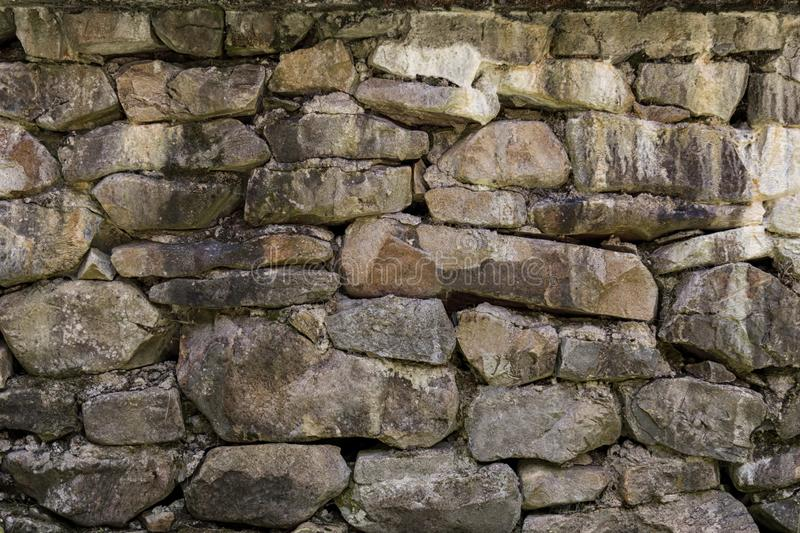 Fragment of old stone wall made of different form and size rocks. Stone texture, background stock photo