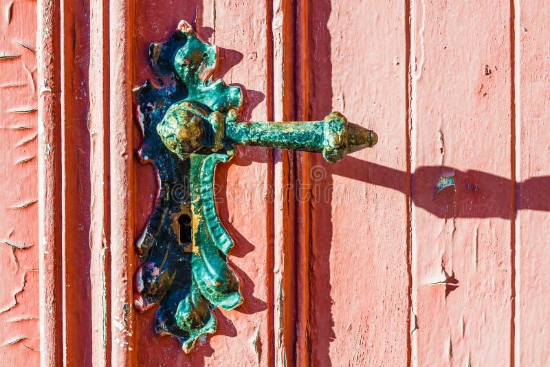 Old weather-beaten red door with old vintage door knob, surface with chapped textured paint. Fragment of old weather-beaten red door with old vintage door knob stock photography