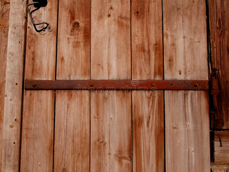 A fragment of an old wooden barn door. With iron canopies on the village farmstead stock photography