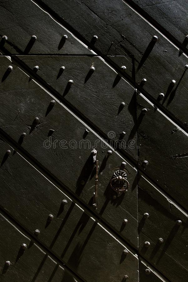 Fragment of Old wooden door with metal ornate hinge. Close up. royalty free stock photos