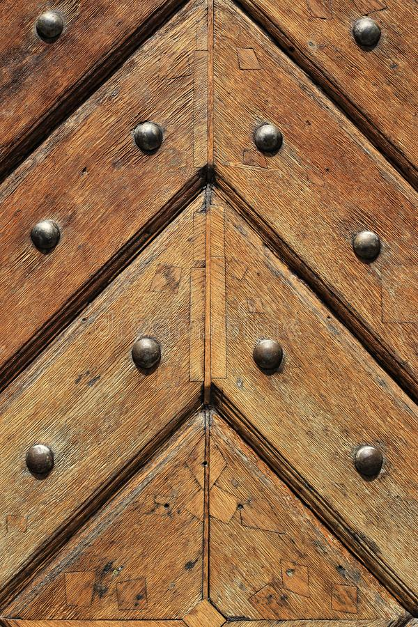 Fragment of old wooden doors with metal rivets. Fragment of old vintage wooden doors with metal rivets, close-up architectural texture stock photography