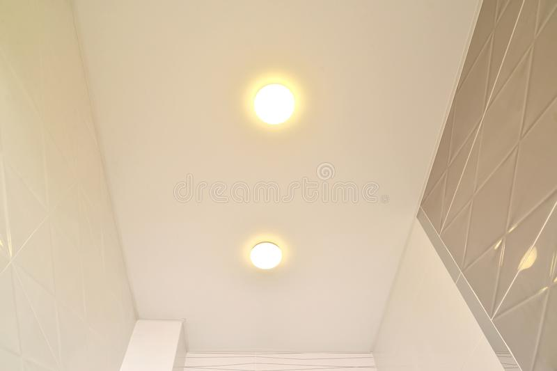 Fragment of an opaque stretch ceiling with lamps in an apartment corridor royalty free stock photography