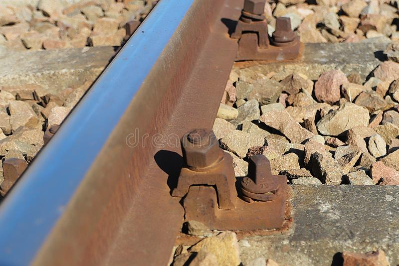 Fragment of a railway bed. Fastening of rails to sleepers with the help of a bolt. Gravel for trains. Technology of transport comm. Unications. Development of royalty free stock images