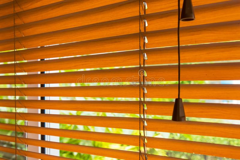 Fragment of the red brown Venetian blinds on a window and blurred view of the autumn trees across slats of a window blind. stock photos