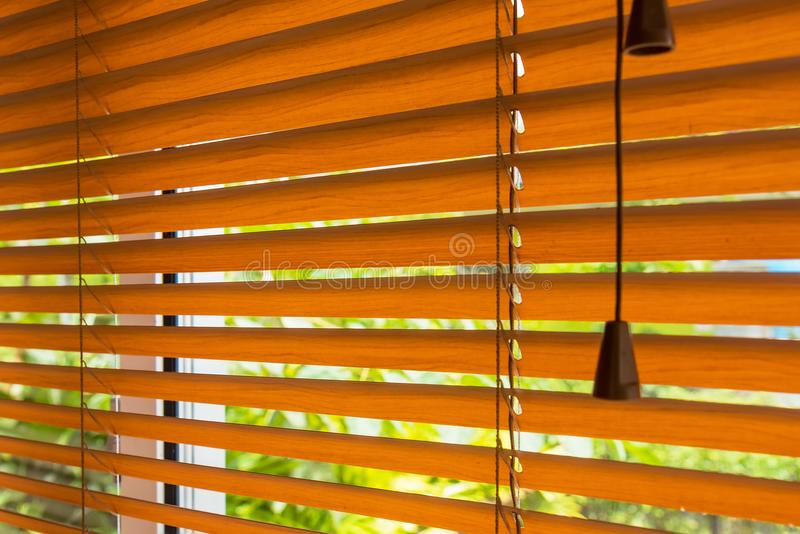 Fragment of the red brown Venetian blinds on a window and blurred view of the autumn trees across slats of a window blind. royalty free stock photography