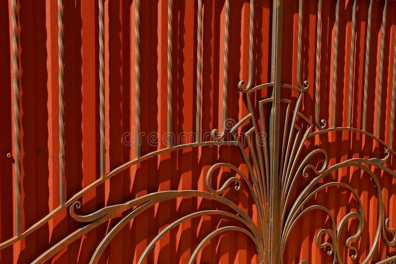 A fragment of red doors with forged bars and a beautiful pattern. The texture of a red iron wall and black steel bars with a pattern stock image